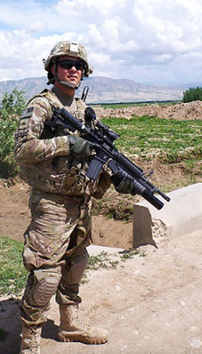 photograph of Sgt. Peter Cassarly in Afghanistan dressed in his combat fatigues holding his rifle